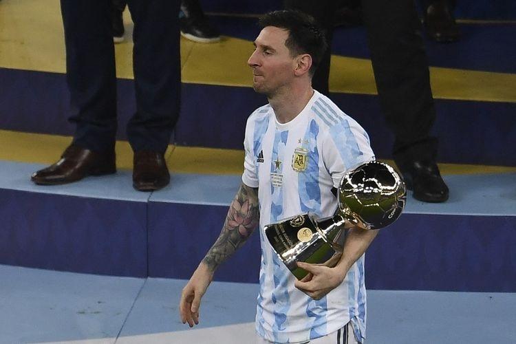 Lionel Messi memegang trofi Top Skor Copa America 2021 setelah timnas Argentina mengalahkan Brasil 1-0 di final yang bergulir di Stadion Maracana pada Minggu (11/7/2021), pagi hari WIB.| Sumber: MAURO PIMENTEL via Kompas.com