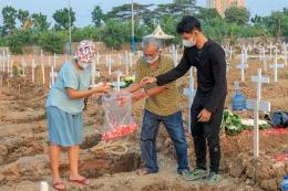 Keluarga menaruh bunga kepada peti jenazah korban Covid-19 di TPU Rorotan Cilincing, Jakarta Utara, Minggu (18/7/2021). (Jonas/Mahasiswa)