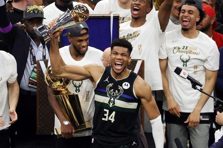Giannis Antetokounmpo memegang trofi MVP NBA Finals saat merayakan kemenangan Milwaukee Bucks atas Phoenix Suns di Game 6 NBA Finals 2021 di Fiserv Forum, Milwaukee, Wisconsin, AS, pada 21 Juli 2021 pagi hari WIB.(Getty Images via AFP/JONATHAN DANIEL)