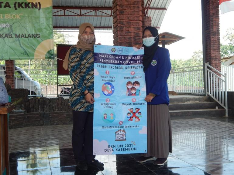 Penyerahan banner protokol kesehatan kepada sekretaris Desa Kasembon