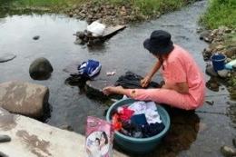 Seorang ibu rumah tangga yang sedang memanfaatkan air sungai untuk mencuci baju, foto: matrapendidikan.com