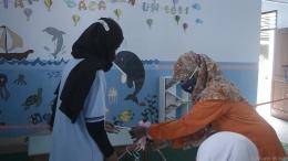 Pemotongan pita sebagai simbol pembukaan taman baca oleh Kepala PAUD dan penanggung jawab program kerja