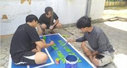 Proses pengecatan papan pantul yang dilakukan oleh Mahasiswa KKN UM