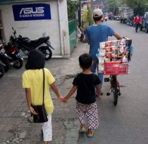Penjual kopi keliling dengan sepeda bersama dua anaknya di jalan menuju Stasiun Pondok Cina. (Foto: Norman Meoko)