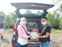 Serah terima donasi buku dari salah satu pendonasi(Foto oleh: KKN UM Pandanmulyo 2021)