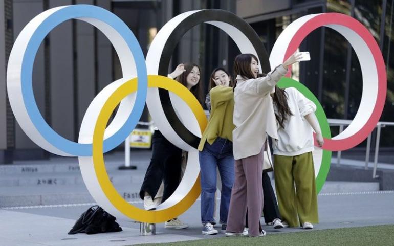 Sejumlah warga berfoto di dekat logo Olimpiade di depan Museum Olimpiade di Tokyo | Sumber: Bloomberg