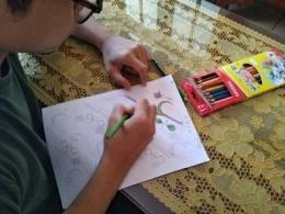 Proses mendesain batik dengan menggambar sketsa dibuku gambar, kemudian diwarnai secara manual/dokpri