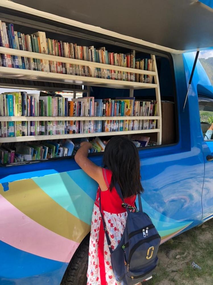 Gambar 1/Dokpri: Anak-anak mengambil buku dari fasilitas yang disediakan oleh perpustakaan keliling