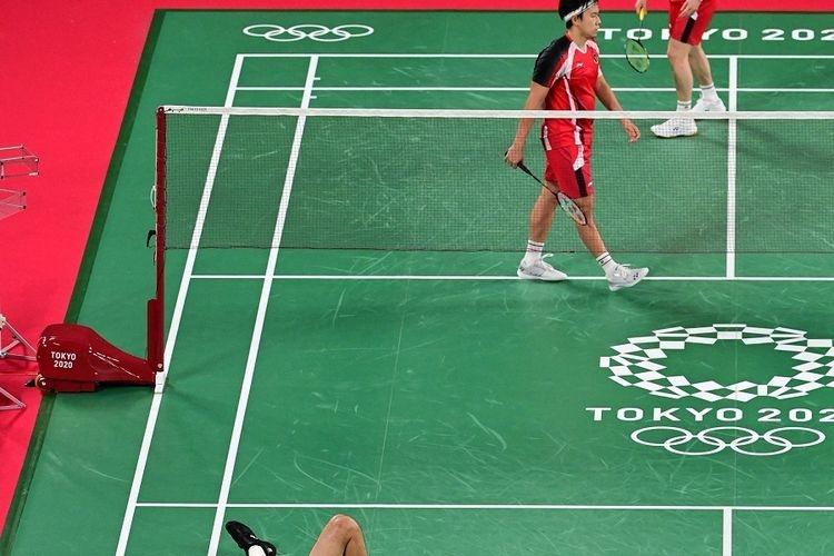 Marcus Fernaldi Gideon dan Kevin Sanjaya Sukamuljo (atas) dalam penyisihan grup ganda putra melawan Wang Chi-lin-Lee Yang dari Taiwan pada Olimpiade Tokyo 2020, pada 27 Juli 2021. (Foto: PEDRO PARDO via kompas.com)