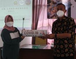 Serah terima kenang-kenangan poster waspada Covid-19 Kelurahan Candirenggo kepada Ibu Mariati selaku Kepala Kelurahan