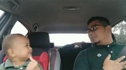 Seorang Ayah yang Bercanda Dengan Anak Ketika Macet. Sumber Tribunnews.com