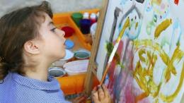 Seorang anak yang tengah melukis sesuatu sesuai dengan imajinasinya (foto dari educenter.id)