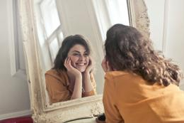 Seorang gadis yang sangat terlihat bahagia di depan cermin. (sumber: pexels/Andrea Piacquadio)