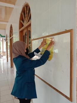 Mahasiswi KKN Tim 2 Undip menempelkan poster #BersamaLawanCorona yang berisi tentang cara memakai masker dengan tepat