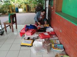 Penulis tengah memilah dan memeriksa buku yang baru dikembalikan.