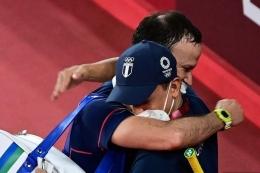 Kevin Cordon memeluk sang pelatih saat memastikan diri lolos ke semifinal usai mengalahkan pebulutangkis Korea di Olimpiade 2020. (kompas.com)