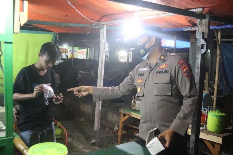 Personel Polda Banten saat memberikan masker kepada salah seorang pelanggar prokes, (dok. Humas Pandeglang)