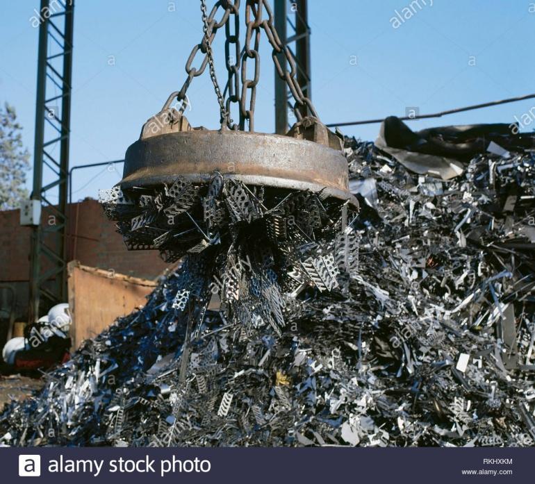 Elektromagnet pada derek mengangkat logam di langsiran besi bekas. Sumber: alamy.com