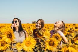 unsplash/Antonino Visalli (Tiga orang gadis yang terlihat begitu bahagia di taman bunga matahari)