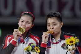 Pasangan ganda putri Greysia/Apriyani mengecup medali emas yang diraihnya di Olimpiade Tokyo (sumber : kompas.com)