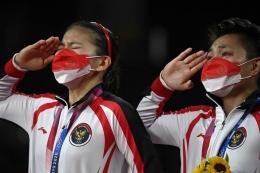 Pasangan ganda putri Indonesia Greysia Polii (kiri) dan Apriyani Rahayu (kanan) memberi hormat dengan medali emas bulu tangkis ganda putri pada upacara Olimpiade Tokyo 2020 di Musashino Forest Sports Plaza di Tokyo pada 2 Agustus 2021. (Foto: AFP/ALEXANDER NEMENOV via Kompas.com)