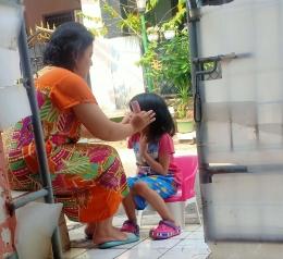Cucu saya Senandung (7 tahun) dirapikan rambutnya oleh ibunya hanya menggunakan gunting dan sisir di rumah (foto Nur Terbit)