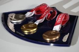 Medali Olimpiade Tokyo 2020, perak (kiri), emas (tengah), dan perunggu (kanan). Foto (AFP/ISSEI KATTO) via tekno.kompas.com