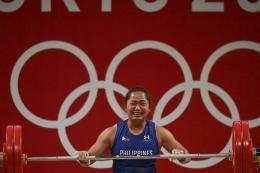 Lifter Filipina Hidilyn Diaz berhasil meraih emas di kelas 55 kg angkat besi putri Olimpiade Tokyo 2020. Senin (26/7/2021).(AFP/VINCENZO PINTO dipublikasikan Kompas.com)