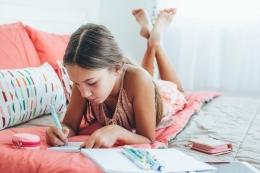 Ilustrasi seorang anak menulis buku evaluasi | Sumber: stock.adobe.com/Alena Ozerova