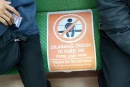 Tanda larangan duduk agar penumpang tidak berdempetan (foto: widikurniawan)