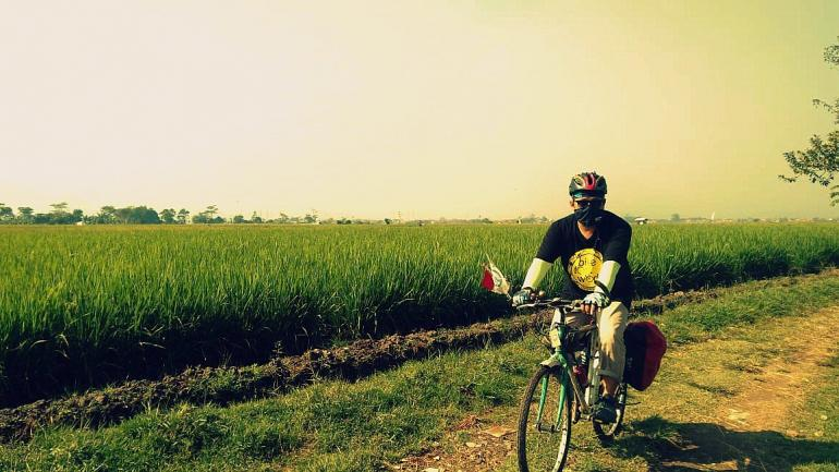Bersepeda susur pinggir pesawahan. Foto : cuham