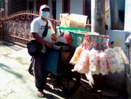 Mas Tanji di samping sepeda motornya yang dipenuhi kontainer/keranjang berisi tempe, tahu, dan aneka dagangan (Foto koleksi Muhamad Nurtanji)