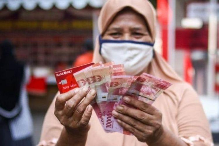 Warga menunjukkan uang bantuan sosial tunai atau BST usai mengambil di ATM Bank DKI, Jakarta, Selasa (20/7/2021).(ANTARA FOTO via KOMPAS.com)