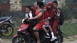Ibu-ibu yang mengantar anak ke sekolah nanti jangan seperti ibu ini. Gambar: BBC.com