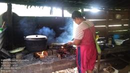 Seorang ibu sedang memanggang daging babi (Marahalim Siagian)