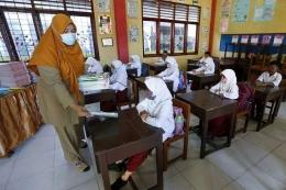 Guru membagikan buku pelajaran kepada pelajar pada hari pertama sekolah tatap muka di SD Negeri 42, Banda Aceh, Aceh, Senin (4/1/2021).  Sumber: ANTARA FOTO/IRWANSYAH PUTRA