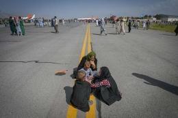 Orang-orang menunggu untuk dapat diberangkatkan dengan pesawat saat mereka berebut untuk melarikan diri ke luar negeri, di Bandara Kabul, Afghanistan, Senin (16/8/2021). Foto: AFP/WAKIL KOHSAR via KOMPAS.com
