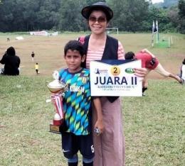 Mario bersama sang ibunda memegang salah satu piala kemenangannya bersama SSB Metro Kukusan (Foto koleksi Ibu Devianna)