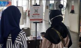 Dua orang penumpang sedang mengunduh aplikasi Peduli Lindungi di stasiun Pasar Minggu (Foto Setiyo)