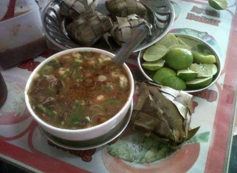 Coto Makassar dalam porsi lengkap: ada ketupat, jeruk nipis dan sambel taucho (foto Nur Terbit)