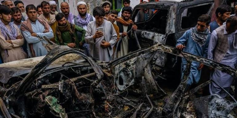 Kerabat dan tetangga dari keluarga Ahmadi berkumpul di kendaraan yang hancur oleh serangan drone AS. 30 Agustus 2021. (Markus Yam/Getty Images)