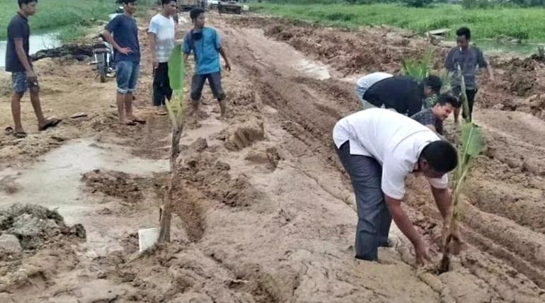 Warga sedang menanam pohon di jalan rusak. (Foto: Kompas.com)