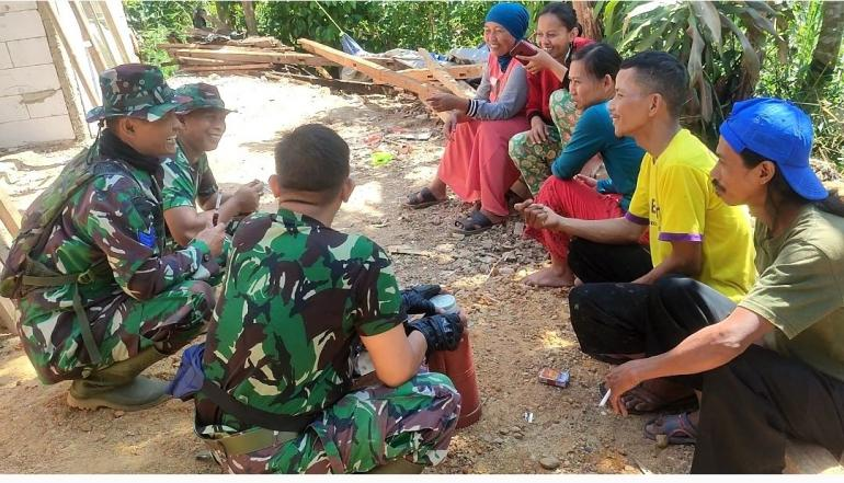 Anggota Satgas TMMD Ke-112 dari TNI-AL sedang berbincang-bincang dengan warga. (Dokpri)