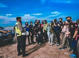 Aparat kepolisisan mberikan sosialisi keselamatan berkendara dan aturan prokes di tempat wisata pantai di Tuban/dokpri