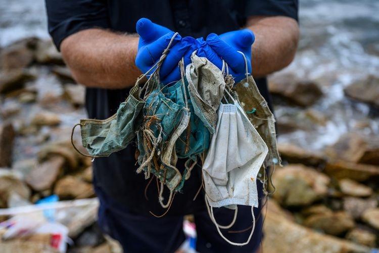 ilustrasi memegang sampah masker sekali pakai yang berserakan di Discovery Bay di Pulau Lantu yang terpencil di Hong Kong.(Foto: AFP/ANTHONY WALLACE via kompas.com)