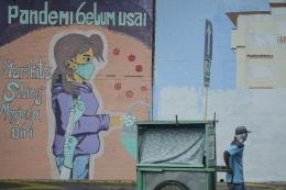 Seorang pedagang menarik gerobaknya dengan latar belakang mural imbauan 'Pandemi Belum Usai di Jakarta, Minggu (18/7/2021). (ANTARA FOTO/M RISYAL HIDAYAT via kompas.com)