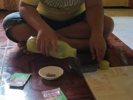 Anak menuangkan air ke wadah (Dokpri)