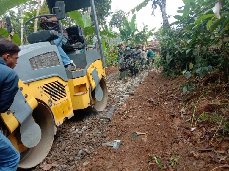 Prajurit TNI Satgas TMMD sedang menarik Stum untuk pengerasan jalan