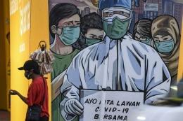 Seorang pedagang yang mengenakan masker melintas di depan mural imbauan untuk melawan COVID-19 di Jakarta, Minggu (29/11/2020).  Sumber: ANTARA FOTO/M Risyal Hidayat/aww.