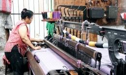 Seorang perempuan sedang mengoperasikan ATM di pabrik tenun Balige (Foto: medanbisnisdaily.com)